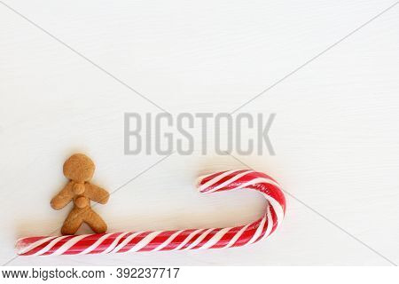 Gingerbread Man And Striped Candy On A Light Background. Sweet Winter Games