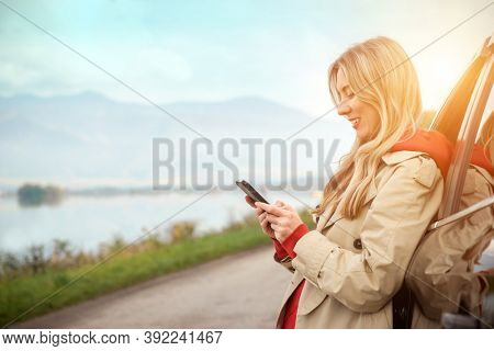 Stylish Woman calling and talking in smartphone, Girl with mobile phone standing near the car in sunny day.