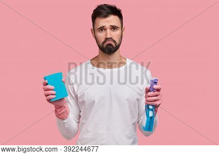 Dejected Gloomy Man With Dark Stubble, Frowns Face In Displeasure, Holds Washing Spray And Sponge, C