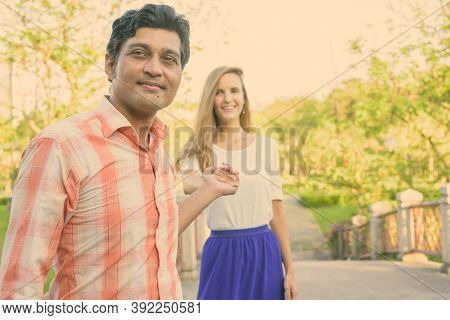 Happy Multi Ethnic Couple Smiling With Indian Man Leading Beautiful Woman While Holding Hands Togeth