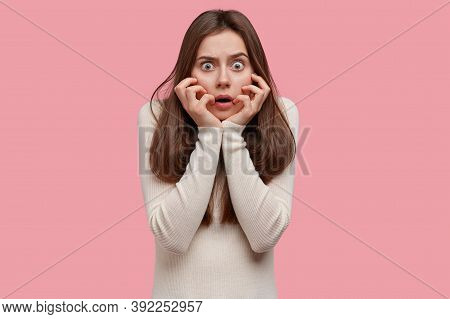 Frightened Shocked Woman Has Eyes Widely Opened, Touches Cheeks, Realizes Some Disaster, Being Frigh
