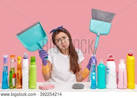 Dejected Upset Young Housemaid Frowns Face In Discontent, Holds Scoop And Broom, Does Cleaning, Wear