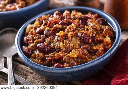 A Bowl Of Delicious Spicy Hot Chili Con Carne With Ground Beef, Onion, Tomato And Red Kidney Beans.