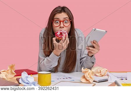 Frightened Emotional Woman With Bugged Eyes, Enjoys Eating Delicious Doughnut, Scared To Be Punished