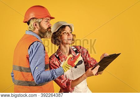 Woman And Man Safety Hard Hat. Discussing Renovation With Contractor. Redevelopment Of Home. Couple
