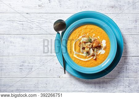 Classic French Main Course: Pumpkin Soup Served On A Blue Plate With  Cream, Croutons And Pumpkin Se
