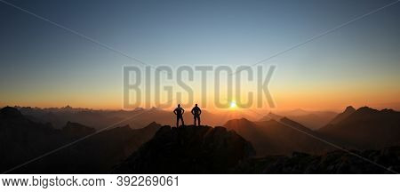 Two Men Reaching Summit Enjoying Freedom And Looking Towards Mountains Sunset.