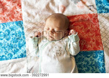 A Little Newborn Sleeping On The Parent Bed