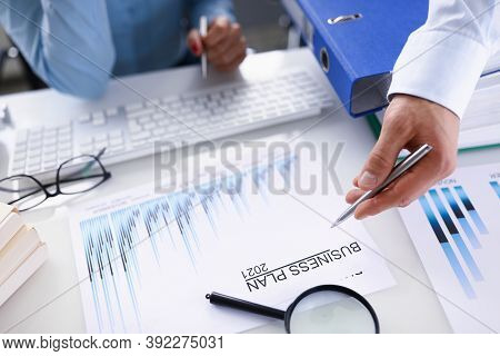 Male Hand Holding Ballpoint Pen Over Business Plan For 2021 Closeup And Female Hand With Keyboard In