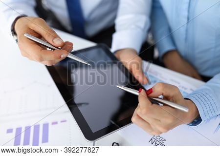 Male And Female Hands Are Holding Ballpoint Pens Over Tablet On Table In Office Closeup. Business Tr
