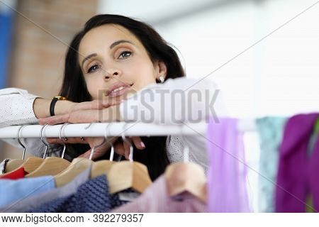 Young Brunette Woman Leaned Her Hands On Rack With Hangers In Store Portrait. Female Business Develo