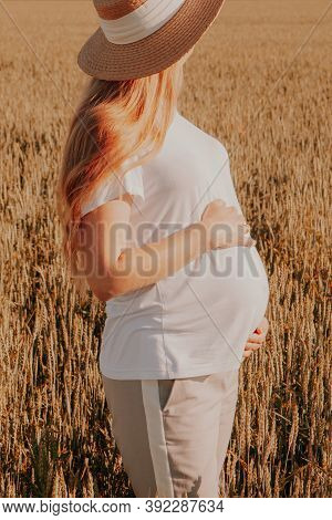 Pregnant Woman Holding Hands Protectively Over Belly\rpregnant Woman Feeling Happy While Taking Care