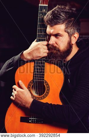 Bearded Guitarist Holding An Acoustic Guitar. Handsome Bearded Man Playing Guitar At The Pub. Practi