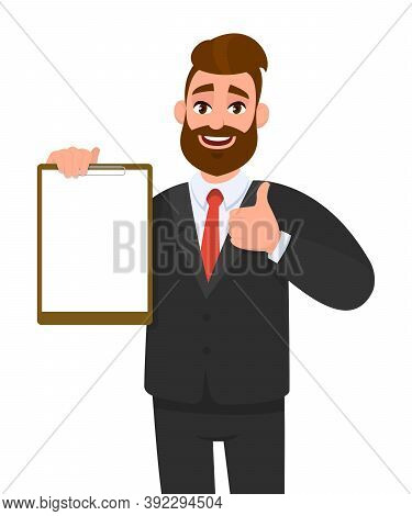 Young Businessman Showing Blank Clipboard And Making Thumb Up Gesture Sign. Person Holding Notepad.