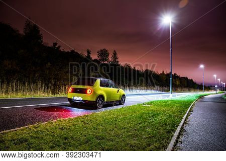 Prague, Czech Republic - October 26, 2020. Night Photo Of Yellow-green Honda E In The Dark Street Af