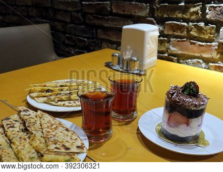 Dinner Of Turkish Traditional Vegetable Tortillas And Black Tea With Dessert Cake