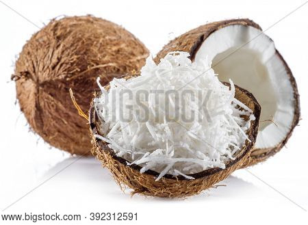 Coconut fruit and shredded coconut flakes in the piece of shell isolated on white background.