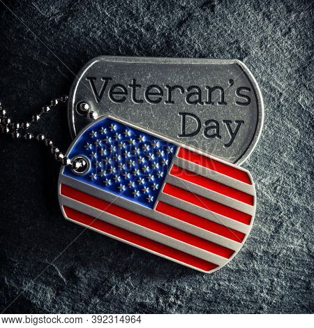 US military soldier's dog tags engraved with Veteran's Day text and in the shape of the American flag.