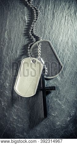 US military soldier's dog tags, rough and worn with blank space for text, and Christian cross necklace. Memorial Day or Veterans Day concept.