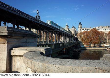 Paris, France - November 21, 2018: Metro train on Bir-Hakeim bridge over Seine river, Fall season sunny day blue sky real moment unfiltered photo