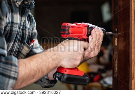Close-up. Carpenter With An Electric Screwdriver Fixes The Plaque For The Lock Of A Wooden Door. Con