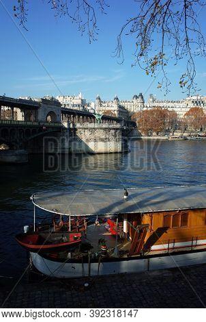 Old boat on Seine river, Bir-Hakeim bridge in autumn season sunny day blue sky real moment unfiltered photo