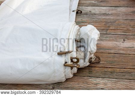 A White Jib Sail Rolled Up On The Dock With Shows A Close Up Of The Bolt Rope And Copper Hanks Sewn
