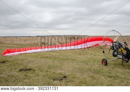 Red And White Canopy Paraglider Lying Green Grass Against Cloudy Sky Background