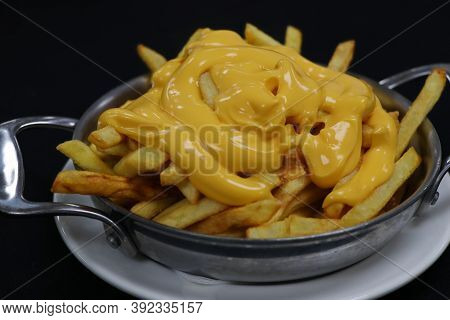 Cheesy French Fries On A Metal Plate With Black Background