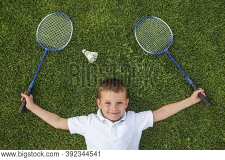 A Smiling Child Holding Two Rackets In His Hands Lies On The Grass Next To The Shuttlecock. Badminto
