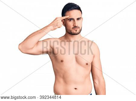 Young handsome man wearing swimwear pointing unhappy to pimple on forehead, ugly infection of blackhead. acne and skin problem