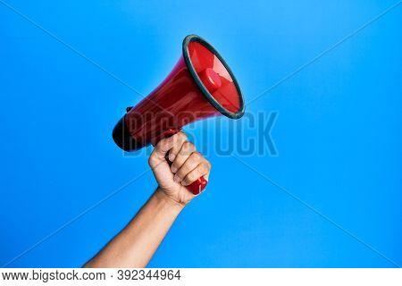 Hand of hispanic man holding megaphone over isolated blue background.
