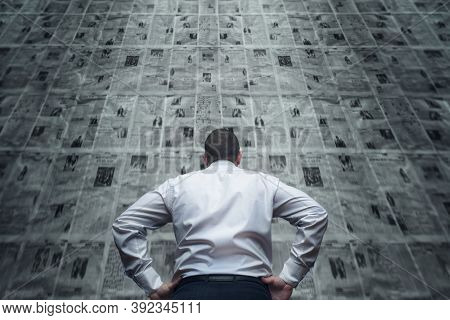 A Man Is Standing In Front Of Newspaper Wall And Reading The Daily Updates. Daily Receipt Of A Large