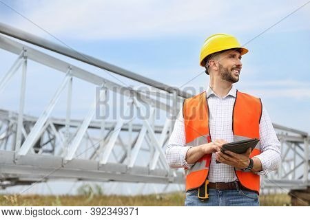 Professional Engineer With Tablet Near High Voltage Tower Construction Outdoors. Installation Of Ele