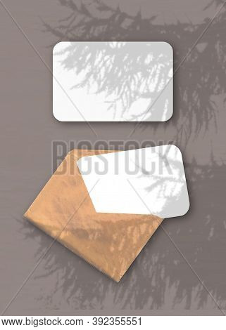 An Envelope With Two Sheets Of Textured White Paper On The Brawn Background Of The Table. Mockup Ove