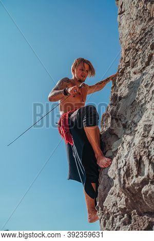 Mature Tattooed Man Holding Sword Ready To Fight And Climbing On The Rock With Background Of Blue Sk