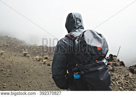 A Hiking Tourist Admiring Climb Mauna Kea Volcano On The Big Island Of Hawaii.