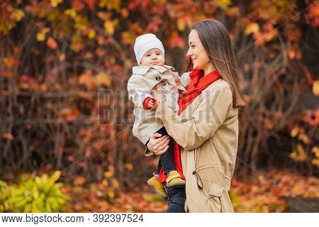Bay With Mom In Autumn Park. Mom And Daughter In The Fall. Mom Holds The Baby In Her Arms. Mother Wi