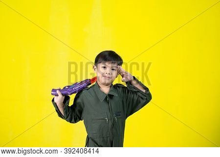 Asian Boy In Military Uniform Holding A Gun, Fun Gestures, Copy Space.
