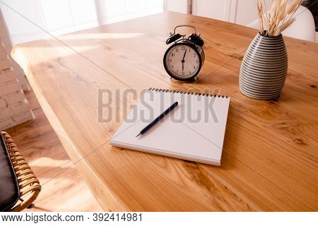Black Alarm Clock, Notepad And Stationary On A Wooden Table. Deadline And Education Concept. Top Hor