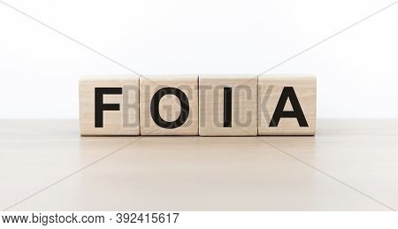 Word Foia. Wooden Cubes With Letters Isolated On Light Background With Copy Space Available. Busines