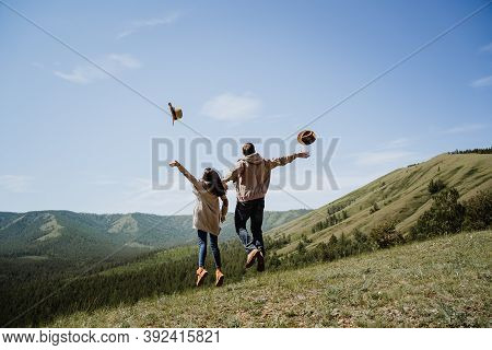 Young Man And Woman Jump Up And Throw Their Hats In The Air, Throw Their Hat In The Sky In Nature, J