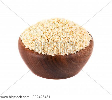 Sesame Seeds In Wooden Bowl, Isolated On White Background. Organic Dry Sesame Seeds.