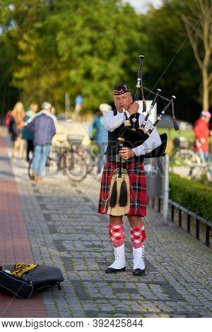 Swinoujscie, Poland - September 06, 2020: Street Musician With Bagpipe On The Beach Promenade Of Swi