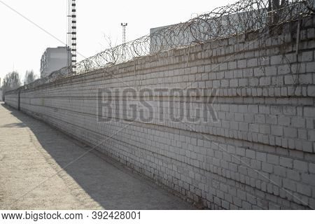 Brick Fence With Barbed Wire Above. The Concept Of Prison Or Private Property. Barbed Wire On A Bric