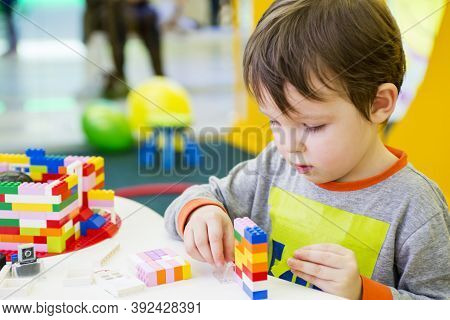 The Child Collects The Designer. Kids Activity In Kindergarten Or At Home. Child Plays With A Childr