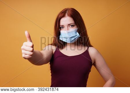 Young Woman Wearing A Medical Face Mask Correctly Covering Mouth And Nose And Giving Thumbs Up - Pro