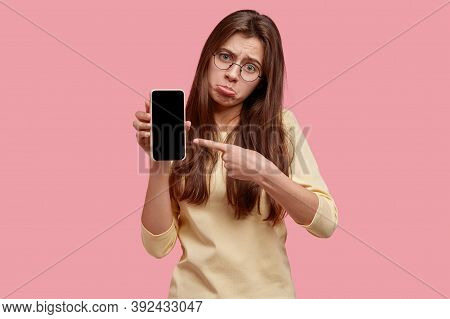 Upset Dejected Woman Purses Lower Lip, Points At Modern Gadget, Shows Empty Screen For Your Text, Do
