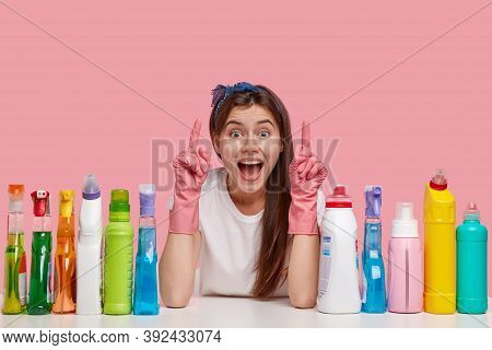 Optimistic Young Housemaid Points Upwards With Both Index Fingers, Wears Headband And Rubber Gloves,