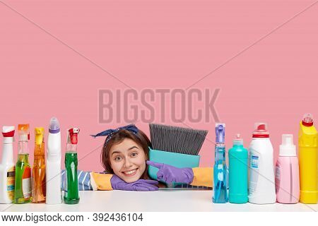 Horizontal Shot Of Satisfied Housemaid Wears Headband, Points At Detergents, Carries Broom Closely,